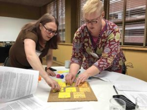 Workshop participants Lee Skallerup-Bassette and Cheryl Ball assemble their group's data visualization